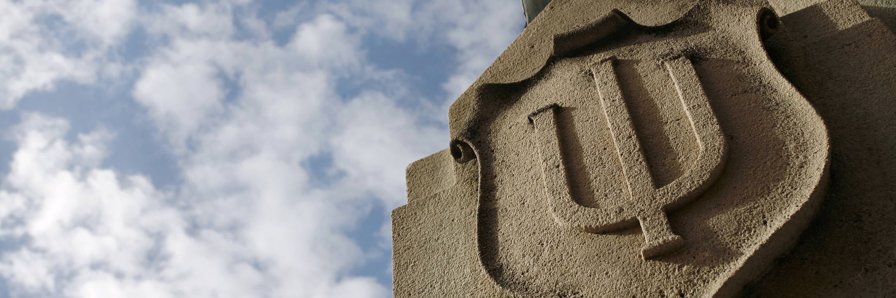The Indiana University trident logo carved into stone.